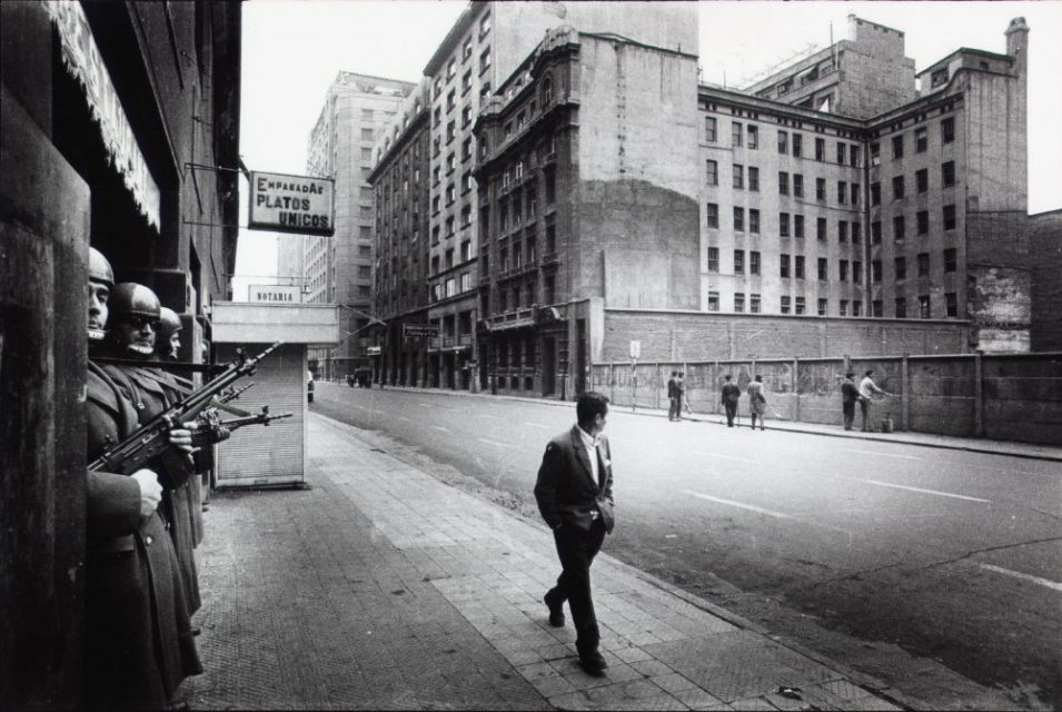 Chili, Santiago, september 1973. People are being forced to remove revolutionary slogans from buildings while militaries are watching.