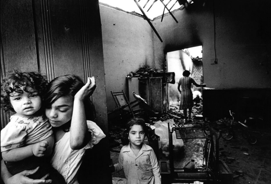 El Salvador, augustus 1990. Woman and children in a destroyed house.
