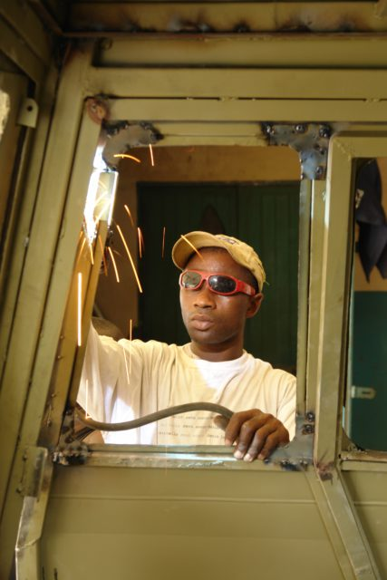 A welder working on one of the Turtle's doors.