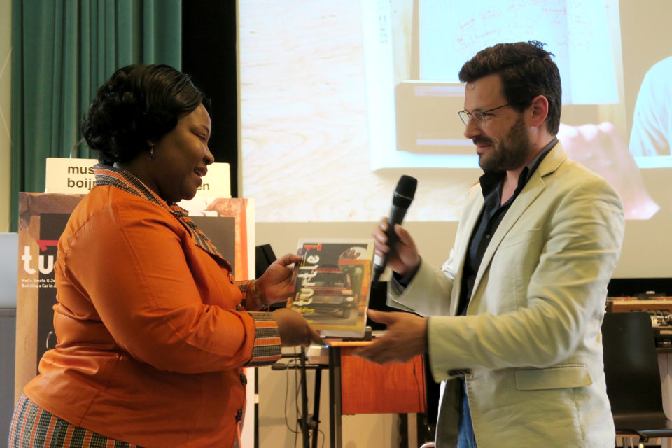 Melle Smets gives the first copy of Turlt 1 to Mvr. Doris A.D. Brese, minister of the Embassy of Ghana