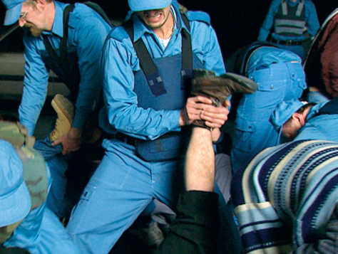 Still from the video Glutinosity (2001). In Glutinosity we see a group of people: in uniforms and activists. Their interaction is theatrical yet ambiguous - who is fighting who?