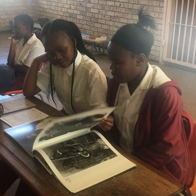 Students having a look at Ad van Denderens photobook 'Welkom in Suid-Afrika'.