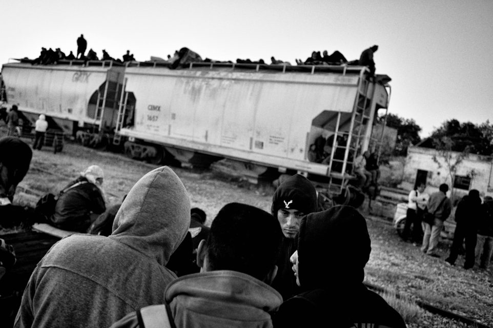 Migrants from central America are waiting in Arriaga for the cargo train to arrive. They will travel on the roof of the train to the US.