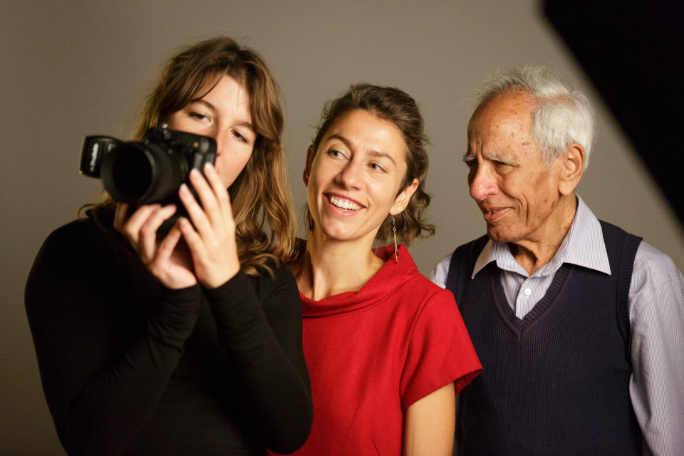 Robin de Puy shows one of her photos to a portrayed father and daughter.