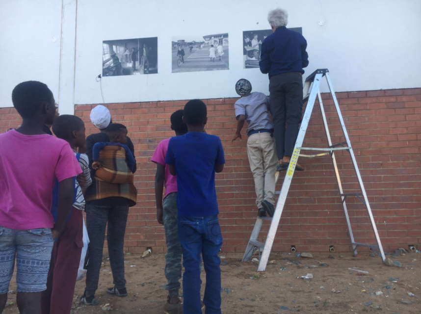 Setting up the exhibition with photos from Welkom in 1992, under the watch of some curious residents.