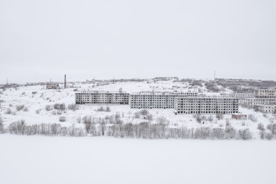 Empty buildings on the banks of the small river Vorkuta.