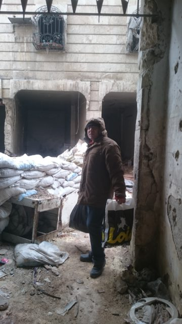 Issa in the entrance of his building. On the back the frontline where the civil war reached Aleppo's street under Touma's window.